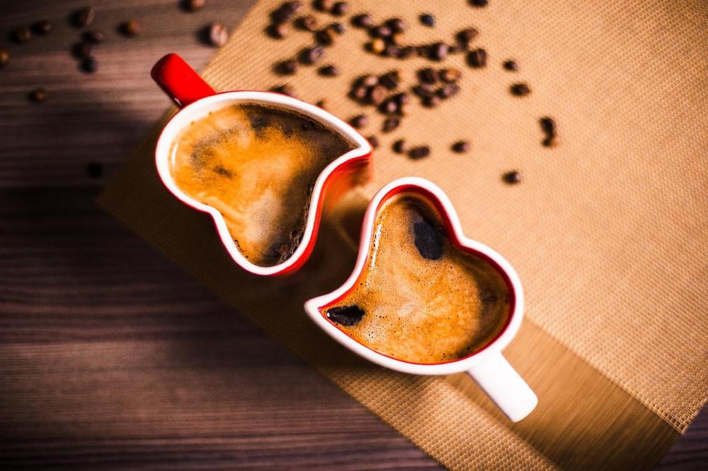 Kaksi sydämen muotoista kahvikuppia, jotka melkein täydentävät toisiaan.