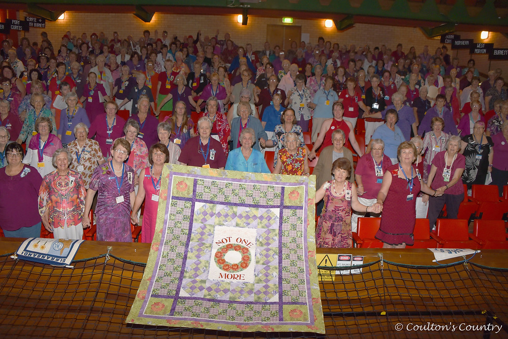 "QCWA Ladies displaying the ""Not One More"" quilt and uniting against domestic violence."
