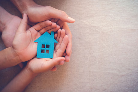 hands holding paper house, family home,
