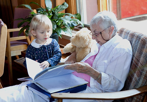 Elder reading to a small girl & her teddy bear