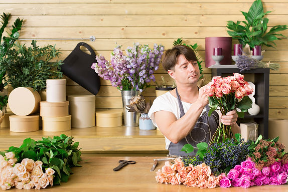 Guy preparing a hand tied bouquet