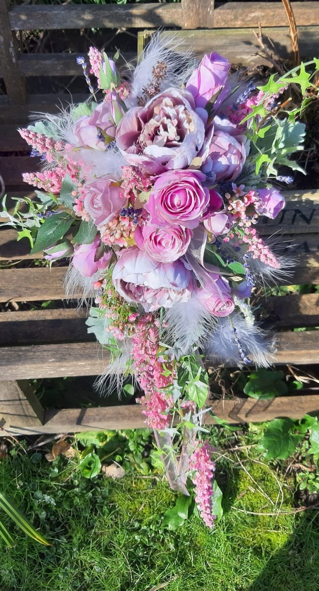 Faux flower bouquet of lilc roses and feathers