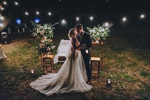Fashionable newlyweds stand at night aga