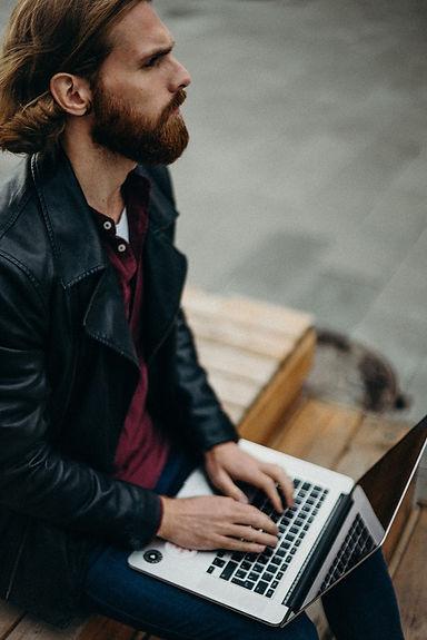 man-wearing-leather-jacket-using-laptop-