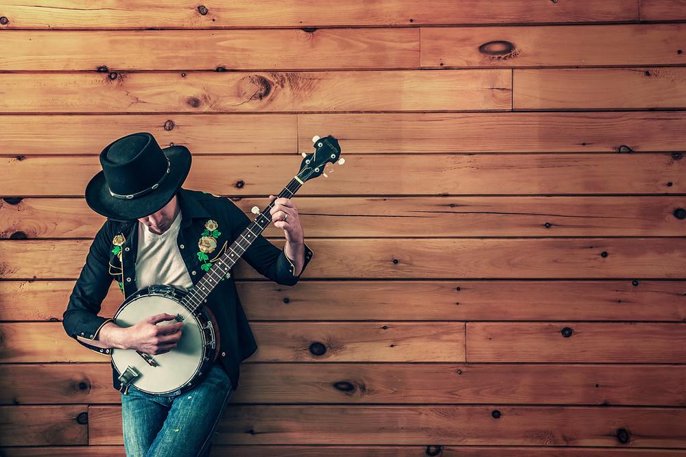 Man wearing country hat playing banjo next to wood paneled wall