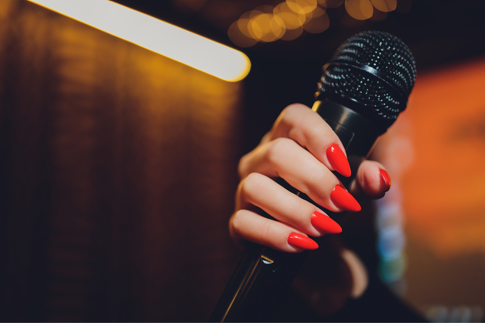 Karaoke-night-at-home-women-with-painted-red-nails-holding-mic
