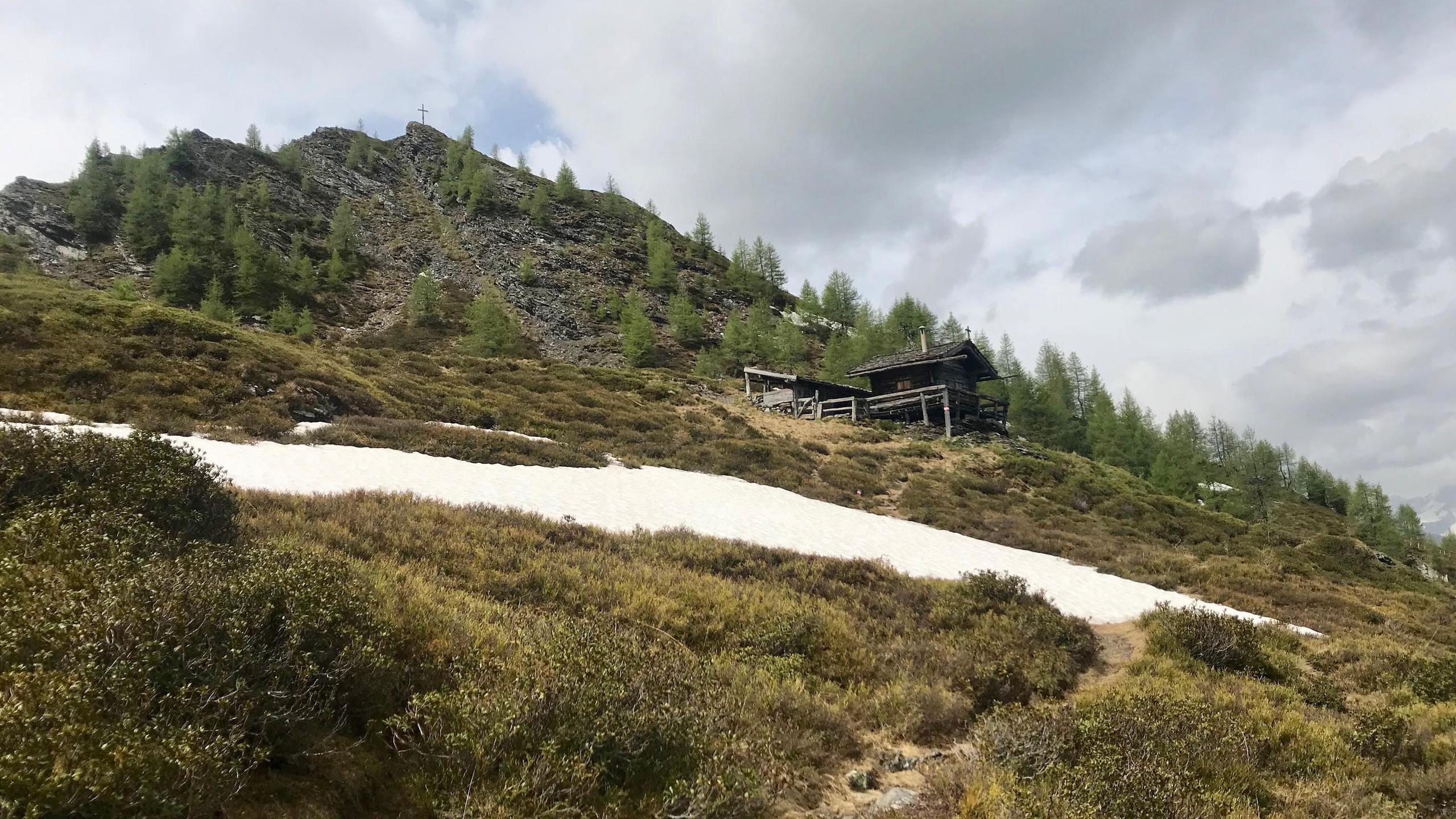 Ottenspitzhuette vor dem Gipfelkreuz der Ottenspitze, Biketour Schmirntal