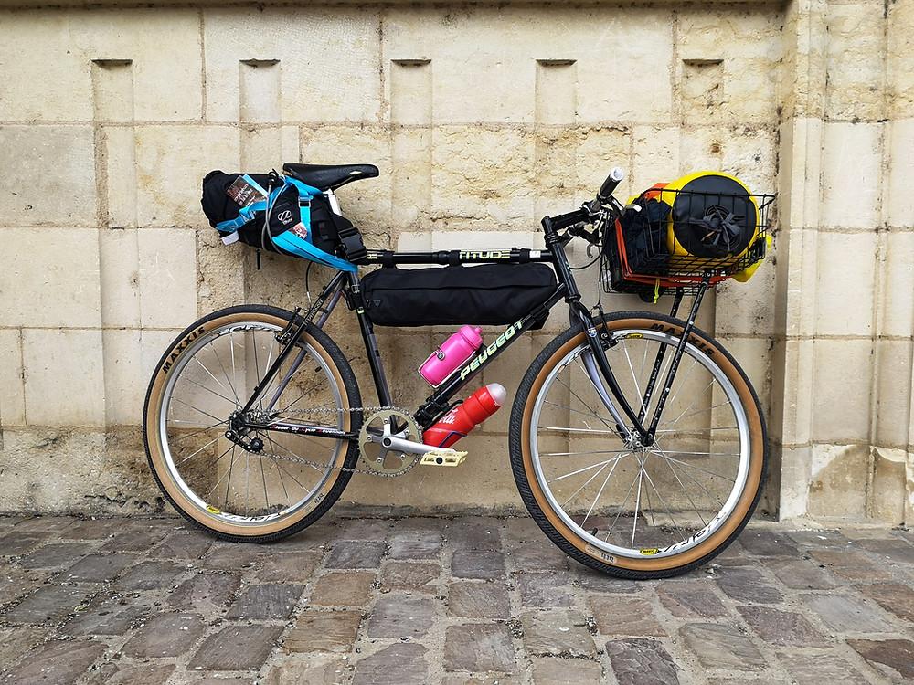 Vieux vélo tout terrain Peugeot devant un mur en pierre