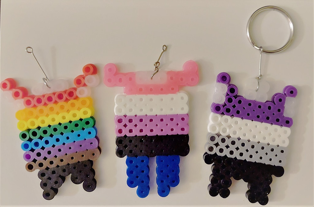 Perler art of abstract monsters. They use the pride colors, gender fluid colors, and ace colors from left to right.