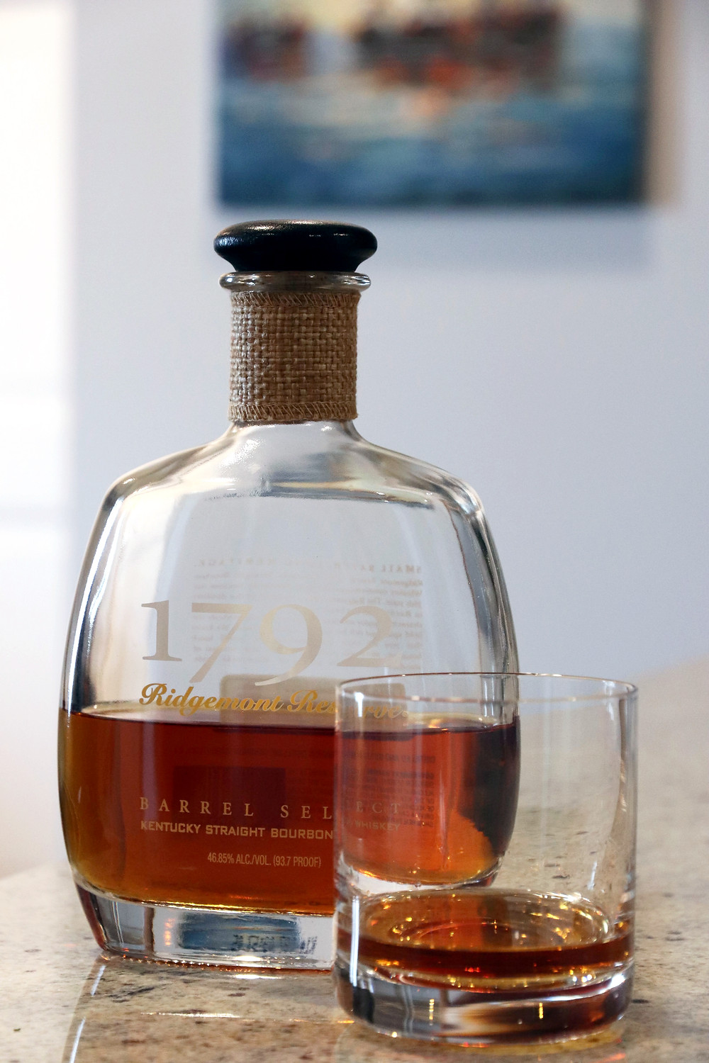 A bottle of 1792 bourbon with a small pour in a glass next to the bottle.