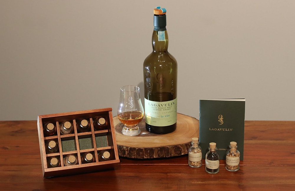 A Bottle of Lagavulin Distiller's edition next to small bottles and a green booklet