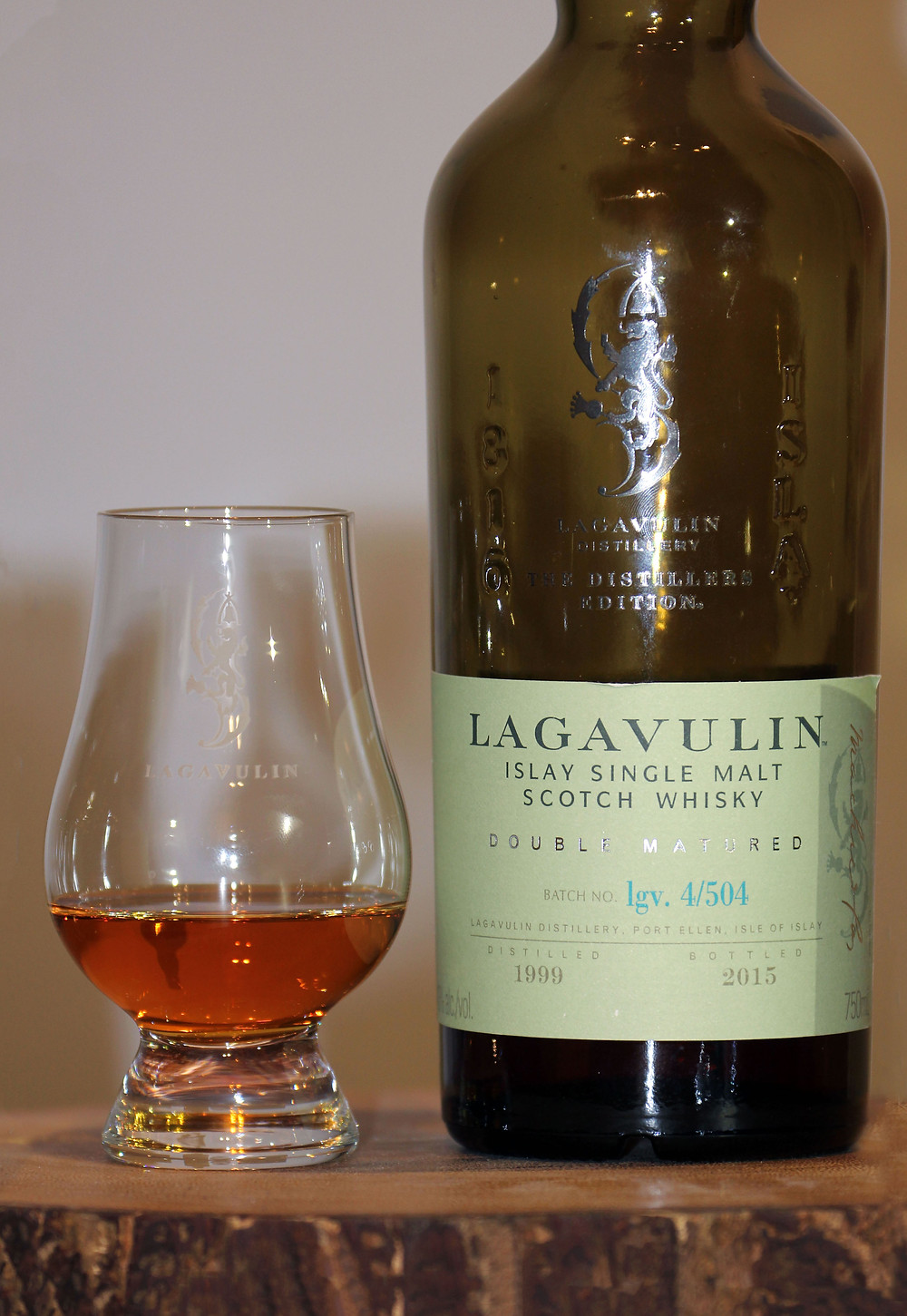A bottle of Lagavulin Distillers Edition on a wooden trivet with a Glencairn glass of amber colored whiskey