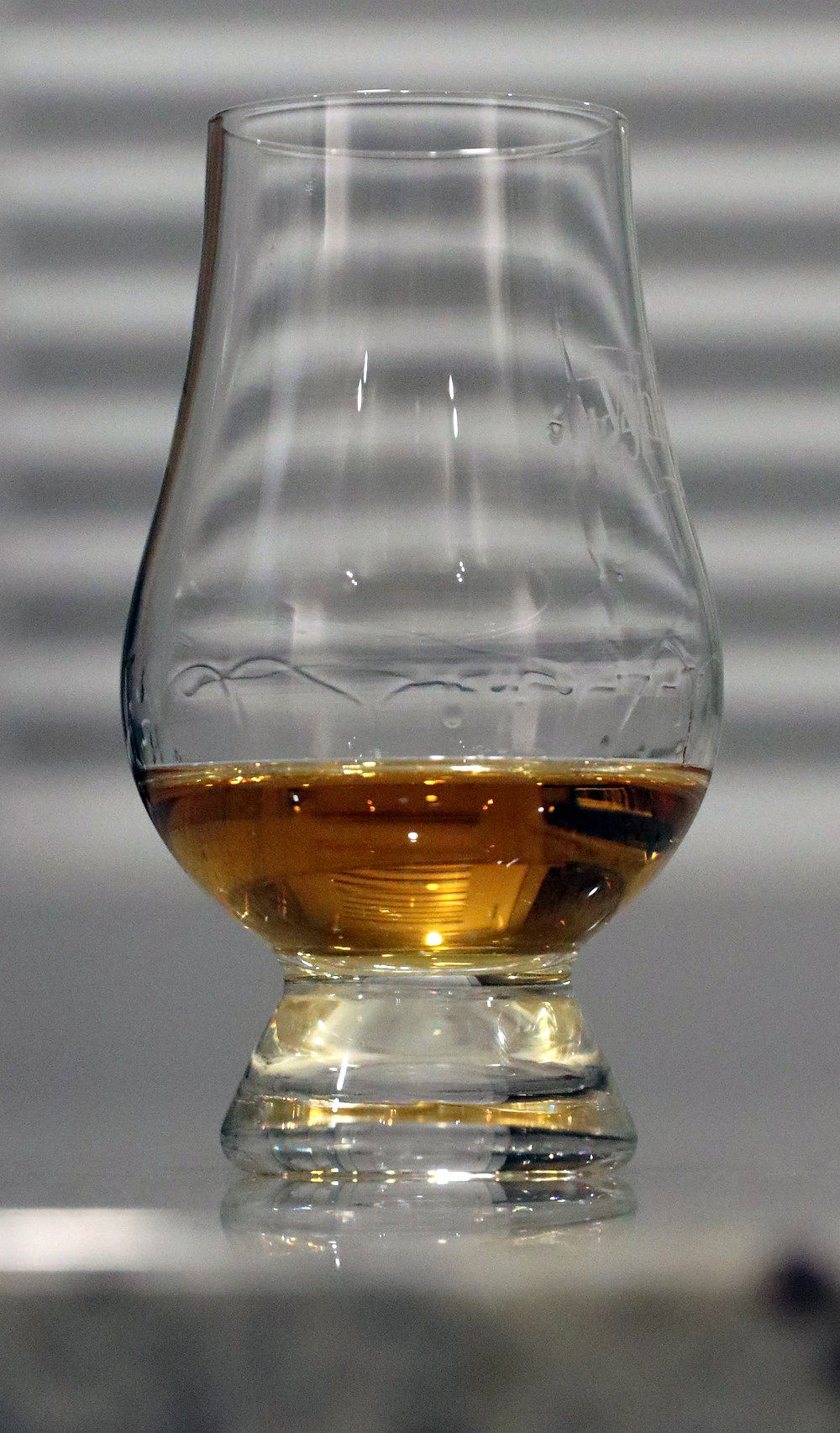 Glencairn glass with honey-colored whisky in it