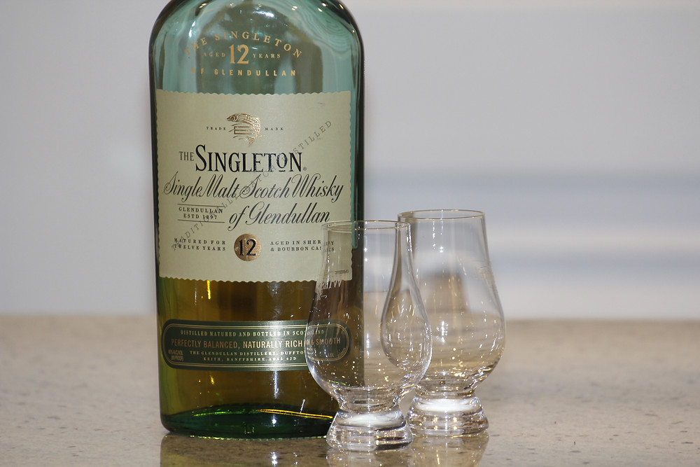 Green Bottle of The Singleton whisky next to two empty Glencairn glasses