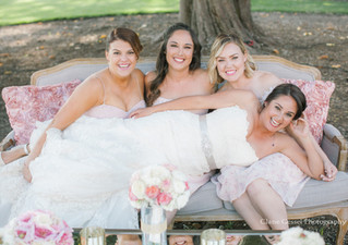 Clane Gessel Photography bridesmaids seated on outdoor couch, laughing bride laying across their laps