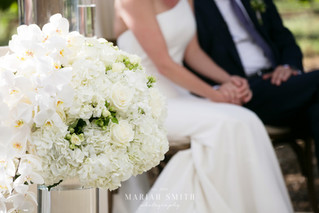 Mariah Smith Photography White floral arrangement Napa wedding couple seated holding hands
