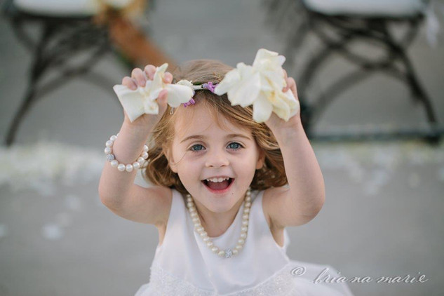 Briana Marie Photography Smiling flower girl holding up rose petals at Napa wedding