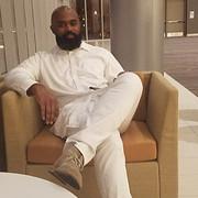 african-american-male-sitting-in-tan-cha