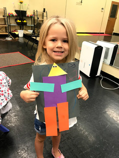 One of our adorable preschoolers posing with her robot!