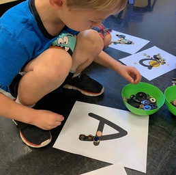 Learning how to write letters by filling them in with beads and buttons!