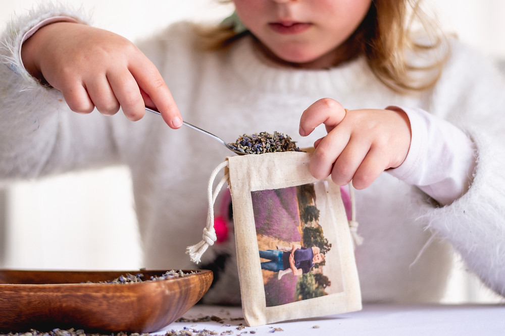 child putting lavender into little bag with photo transfer