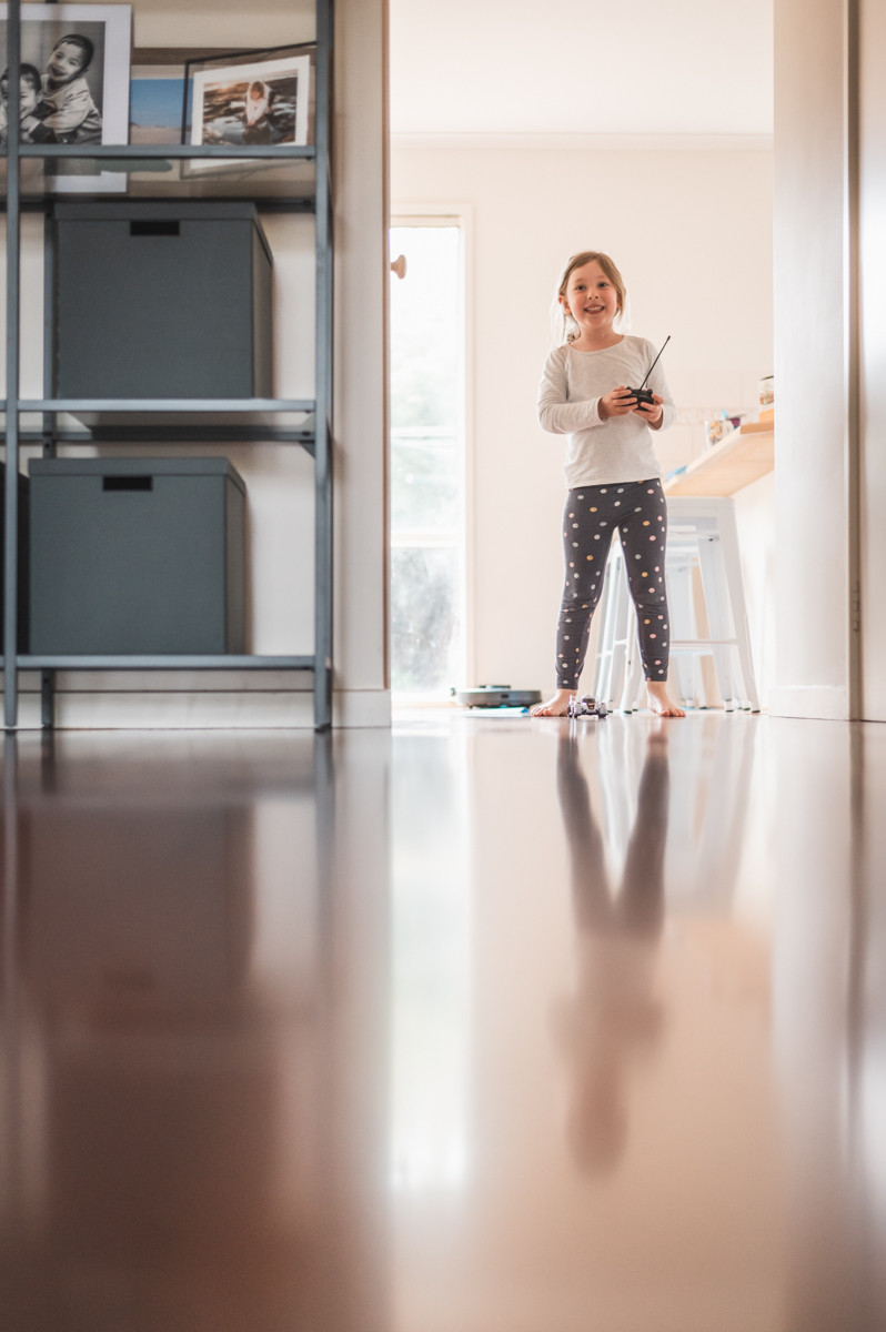 girl holding a remote driving a remote controlled toy car, her reflection is mirrored on the floor. documentary family photography melbourne