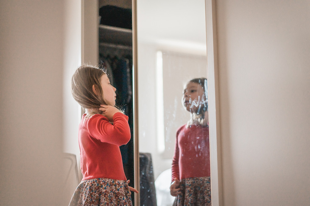 child looking at her reflection in a mirror with her name smeared in the mirror. documentary family photography melbourne