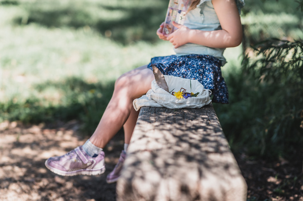 child sitting on a park bench with a bag of flowers she's collected. her head is cropped off at her shoulders. documentary family photography melbourne