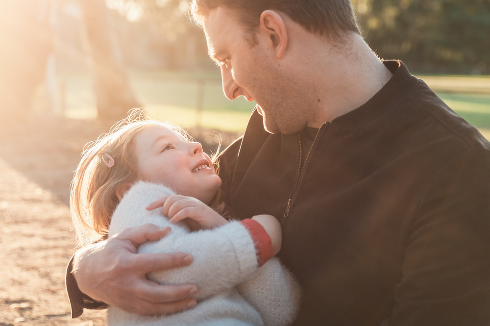 father holding daughter in hazy golden sunlight - outdoor family photography Melbourne