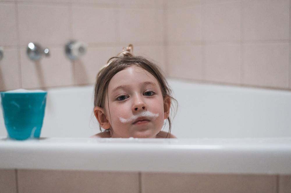 child with a soap bubble mustache in the bath