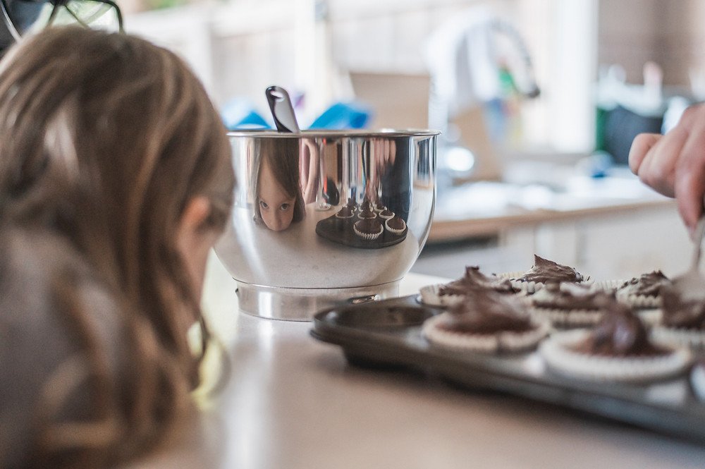 child  looking at her reflection in a mixing bowl. documentary family photography melbourne