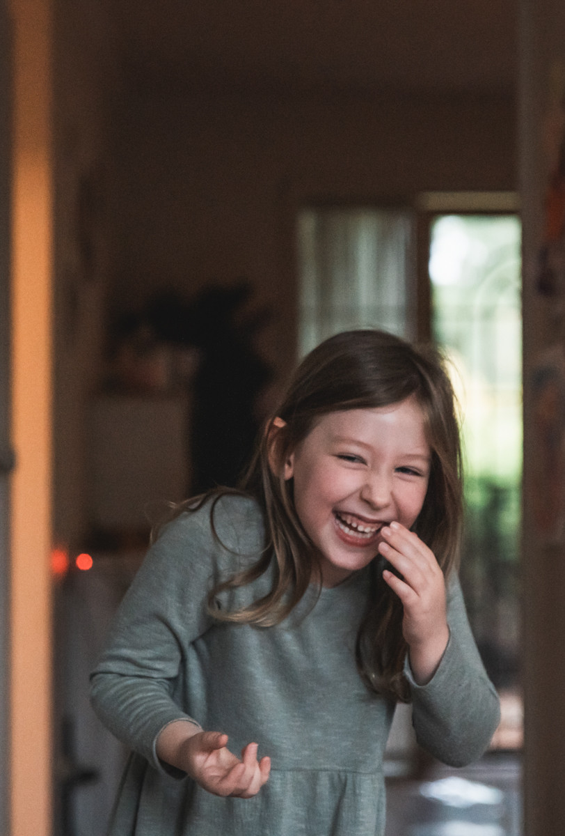 girl laughing while holding her hand up to her face. documentary family photography melbourne