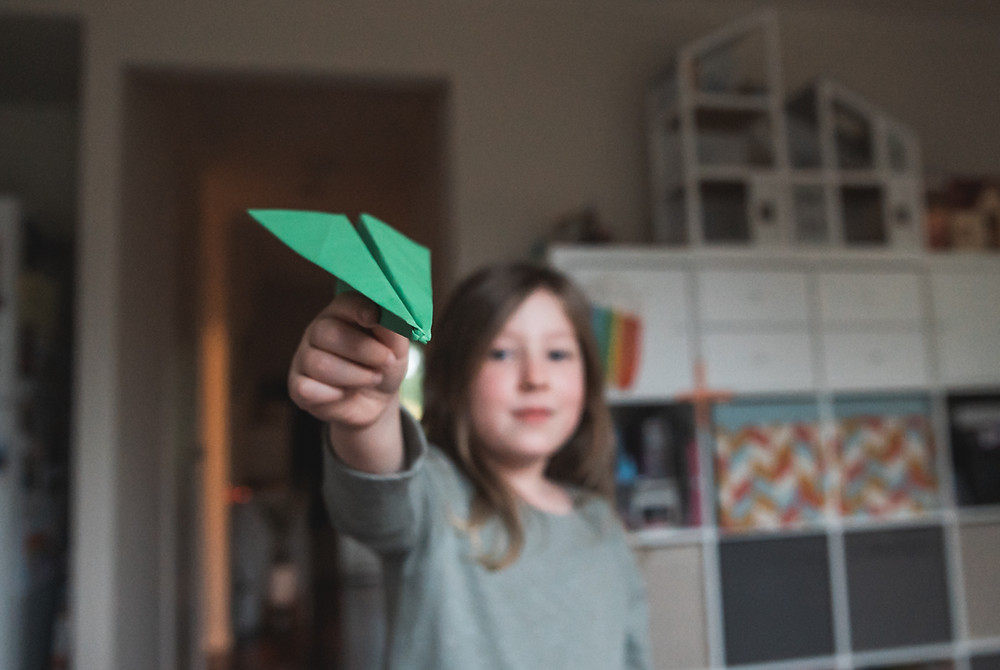 detail shot of a paper airplane being held by a child. Melbourne documentary photography