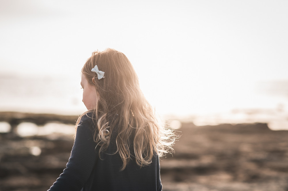 back of a child with her hair catching the golden sunlight