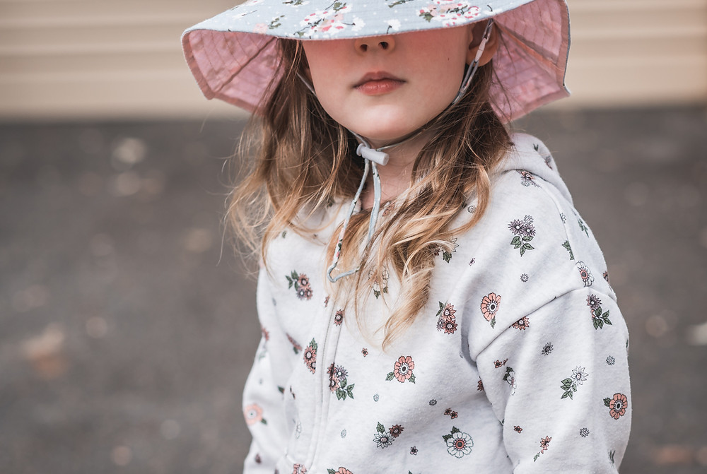 portrait of a girl with her hat pulled down. documentary family photography melbourne