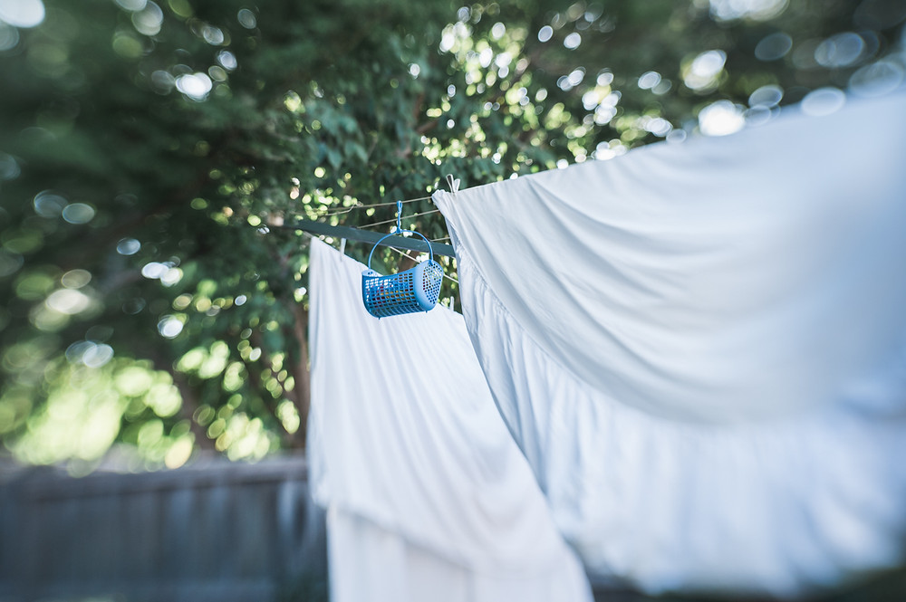 peg basket hanging on a clothes line with white sheets. documentary family photography melbourne