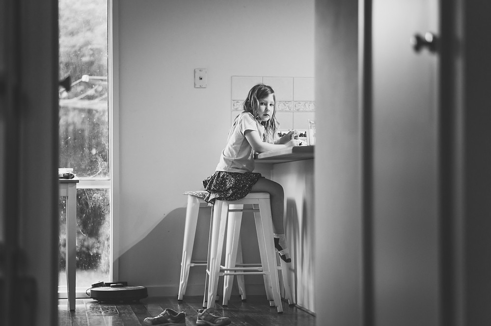 low angle shot of a child sitting at a kitchen counter with her shoes on the floor. Melbourne documentary photography