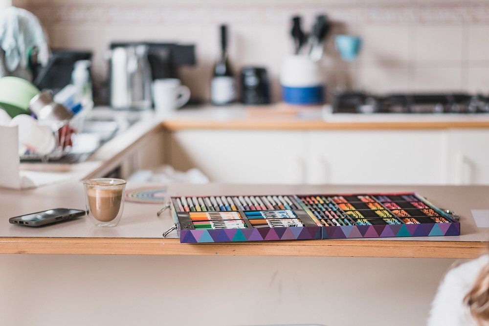 kitchen counter with a cup of coffee, cell phone and pencil case with rainbow colours. documentary family photography melbourne