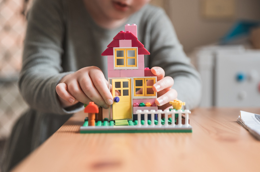 Close up shot of a child playing with a house made of lego. Close up of her hands. Melbourne documentary photography