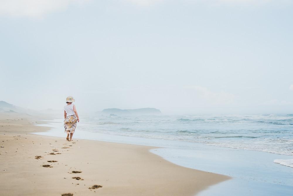 lifestyle image of child walking on misty beach alone