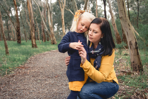 mother and daughter looking at a flower during a photoshoot