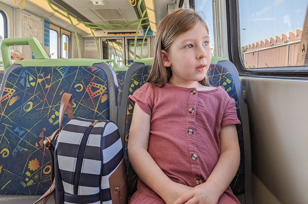 child sitting on a train looking out the window. family photography melbourne