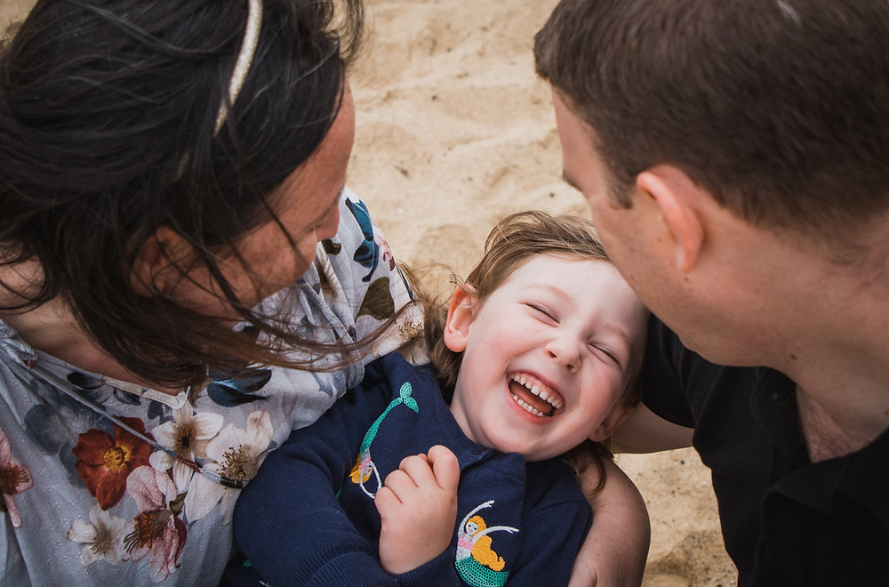 little girl laughing in her parents arms - natural style photography melbourne