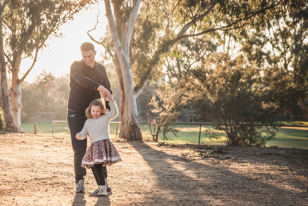 father and daughter dancing in golden sunlight - outdoor family photography Melbourne