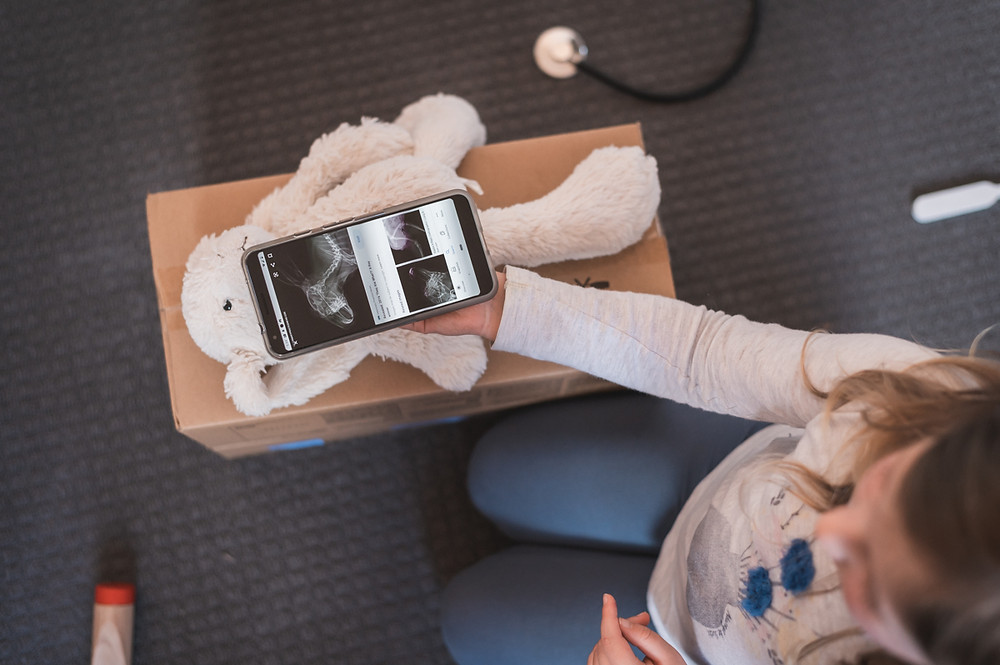 Birdseye view of a child playing doctors, holding a cell phone with xray pictures on it, over a toy rabbit. Melbourne documentary photography