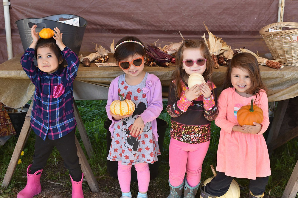 Girls holding mini pumpkins