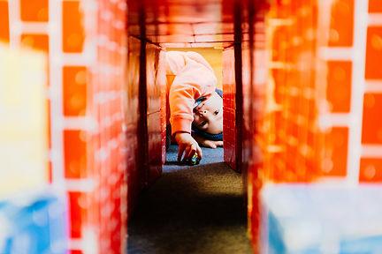 Child looking through block tunnel