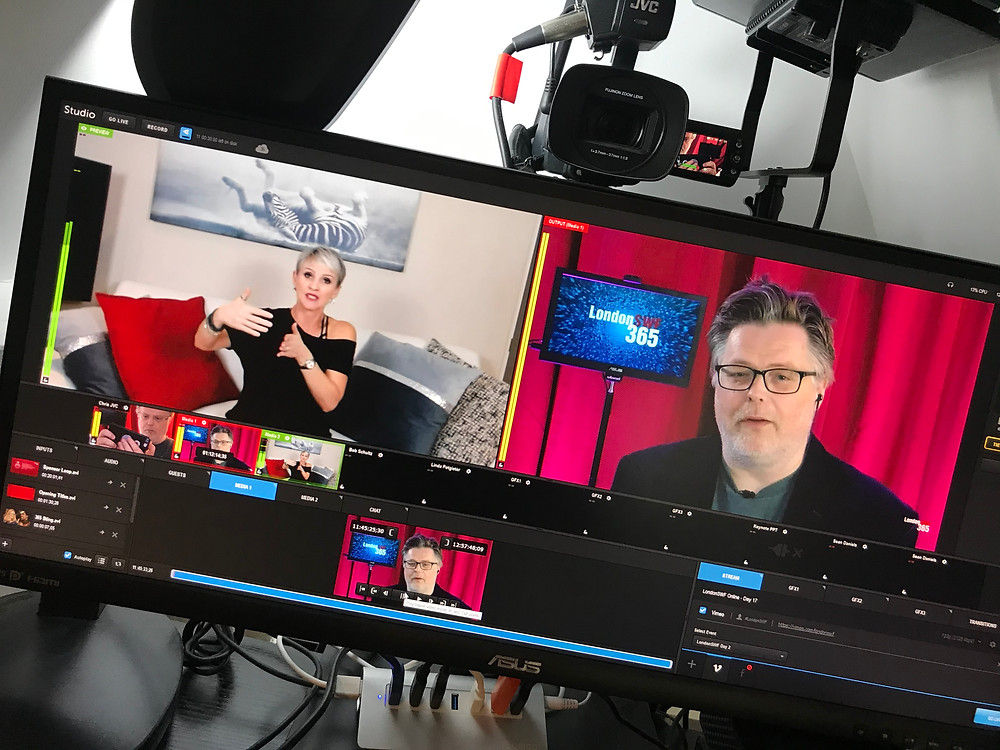Image shows monitor in studio with a guest and the host of the festival