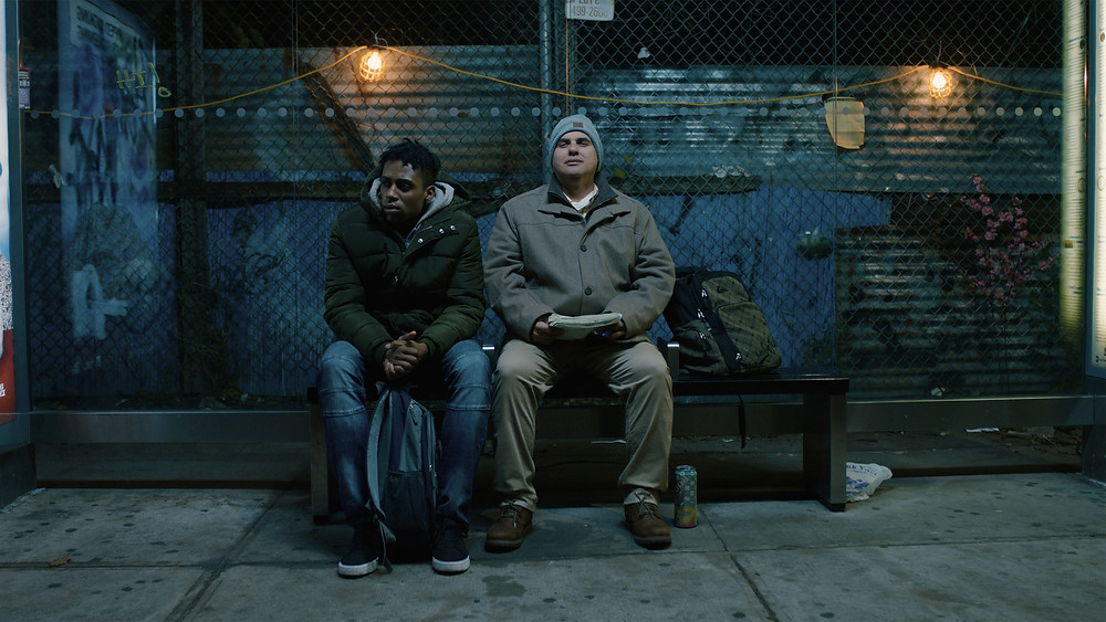 Picture of the two main characters sitting at a bus stop at night