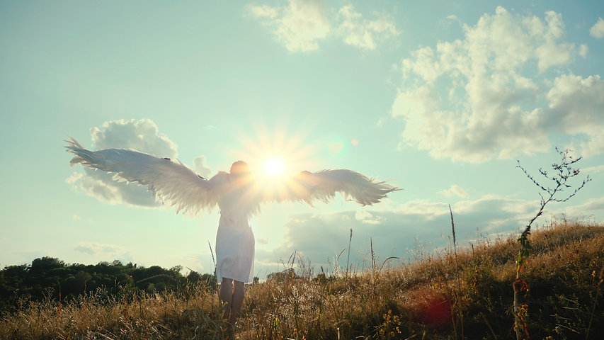 Rear view of beautiful girl angel on a hill raised its wings up and enjoys the sun and sun